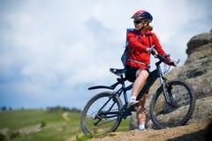 Menina que dá um ciclo nas montanhas Imagens de Stock