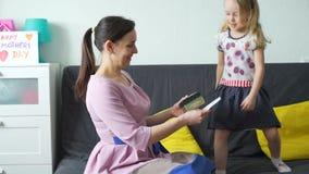 Menina que dá um presente e um cartão a sua mamã filme