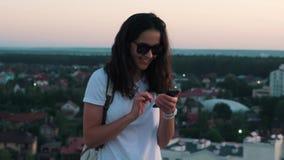 Menina que datilografa no telefone no telhado filme