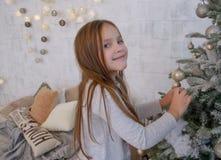 Menina que decora a árvore de Natal Imagens de Stock Royalty Free
