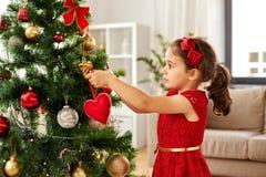 Menina que decora a árvore de Natal em casa fotos de stock royalty free