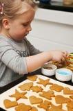 Menina que decora bolinhos do Natal Fotos de Stock