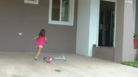 A menina que deixa cair seu 'trotinette' na frente de sua casa e entra para dentro video estoque
