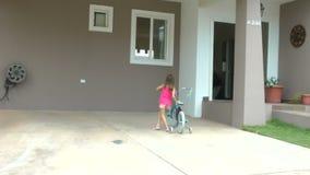 A menina que deixa cair sua bicicleta na frente de sua casa e entra para dentro video estoque
