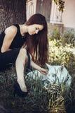 Menina que descansa com cão de puxar trenós branco fotografia de stock royalty free