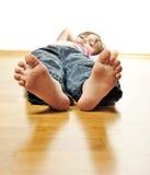 Menina que descansa em um assoalho de madeira Fotos de Stock Royalty Free