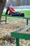 Menina que descansa em um banco Fotografia de Stock Royalty Free