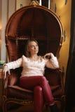 Menina que descansa em uma cadeira Imagem de Stock