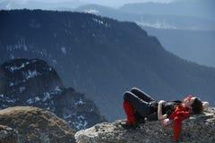Menina que descansa em uma rocha Fotos de Stock
