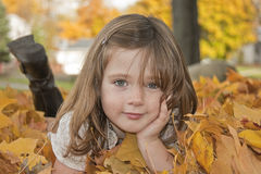 Menina que descansa nas folhas Foto de Stock