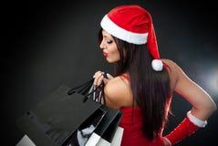 Menina que desgasta a roupa de Papai Noel com saco de compra Fotografia de Stock Royalty Free