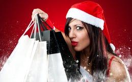 Menina que desgasta a roupa de Papai Noel com saco de compra Fotografia de Stock