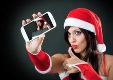 Menina que desgasta a roupa de Papai Noel com smartphone Fotografia de Stock