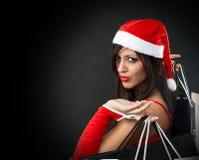 Menina que desgasta a roupa de Papai Noel com vagabundos da compra Fotos de Stock Royalty Free