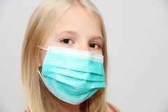Menina que desgasta uma máscara protetora Foto de Stock