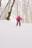 Menina que desliza abaixo do monte no esqui Fotos de Stock Royalty Free