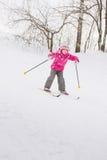 Menina que desliza abaixo do monte no esqui Imagens de Stock Royalty Free