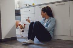 Menina que discute seu cão na cozinha fotos de stock