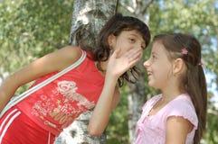Menina que diz um gracejo Fotografia de Stock