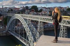 A menina que do viajante o fotógrafo com dreadlocks louros é toma a foto Dom Luis eu construo uma ponte sobre sobre o rio de Dour fotografia de stock