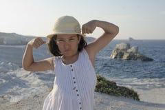 Menina que dobra os músculos na praia Fotos de Stock Royalty Free