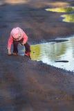 Menina que dobra-se à terra que joga na poça grande da mola que veste o nylon roxo e o chapéu cor-de-rosa da cubeta Imagem de Stock Royalty Free