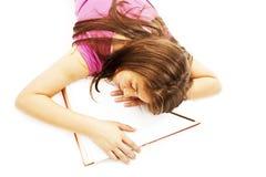 Menina que dorme com sua cabeça em um livro aberto fotos de stock
