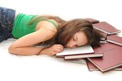 Menina que dorme com sua cabeça em um livro aberto Imagens de Stock Royalty Free
