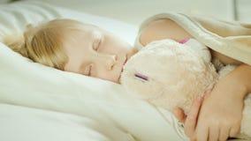 Menina que dorme na cama com seu brinquedo do animal de estimação vídeos de arquivo