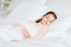 Menina que dorme na cama em casa Fotos de Stock Royalty Free