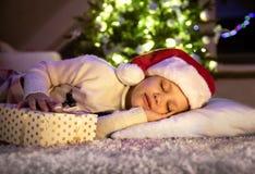 Menina que dorme sob a árvore de Natal imagens de stock