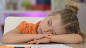 Menina que dormem na tabela e sorriso, cansado após a pintura, tendo o bom sonho vídeos de arquivo