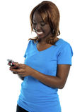 Menina que emite a mensagem através de seu telemóvel Foto de Stock