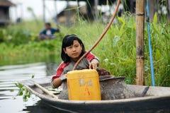 Menina que enche uma lata com a gasolina no lago Inle em Burma, Ásia fotos de stock royalty free