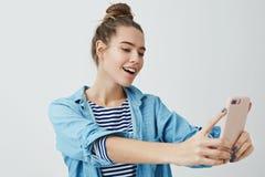 Menina que encontra o ângulo para tomar o selfie impressionante para afixar o Internet em linha Mulher elegante à moda atrativa foto de stock royalty free
