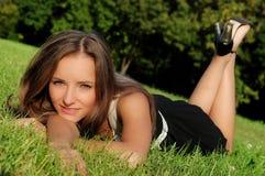 Menina que encontra-se ao ar livre na grama Imagens de Stock