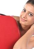 Menina que encontra-se atrás da mala de viagem vermelha Imagens de Stock