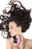 Menina que encontra-se com as flores coloridas em seu cabelo Fotografia de Stock