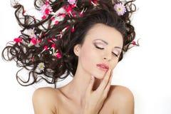 Menina que encontra-se com as flores vermelhas brilhantes em seu cabelo Imagem de Stock Royalty Free