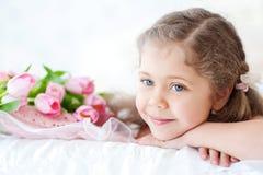 Menina que encontra-se com tulipas cor-de-rosa Imagens de Stock Royalty Free