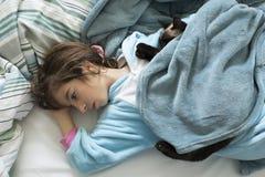 Menina que encontra-se e que pensa sobre a cama Fotos de Stock