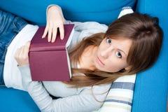 Menina que encontra-se e que prende o livro Fotografia de Stock Royalty Free