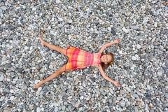 Menina que encontra-se em pedras no seacoast de pedra foto de stock