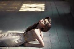 Menina que encontra-se em um assoalho de madeira Imagens de Stock
