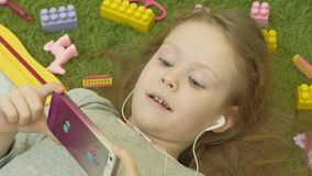 Menina que encontra-se em um fundo verde nos fones de ouvido e que usa um telefone, vista superior filme