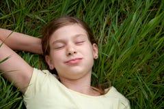 Menina que encontra-se em um prado na natureza Fotos de Stock Royalty Free
