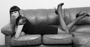 Menina que encontra-se em um sofá no escritório imagem de stock royalty free