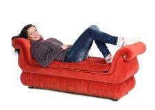 Menina que encontra-se em um sofá vermelho isolado no branco foto de stock