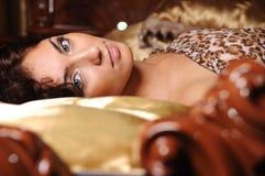 Menina que encontra-se em uma cama Fotos de Stock