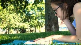 Menina que encontra-se em uma grama no parque e que lê um livro vídeos de arquivo